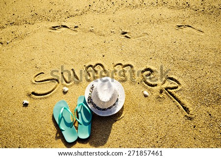 composition on the sand with summer word and hat with shales - stock photo