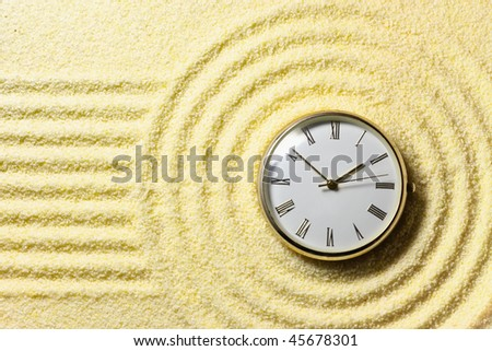 Composition on Zen garden - yellow sand, and watch - stock photo