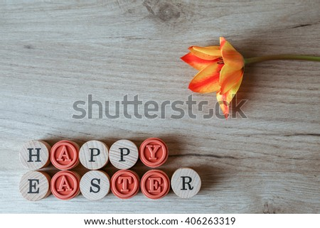 Composition set of Happy Easter text and tulip flower, top view - stock photo