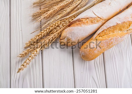 composition two baguettes ears of wheat and rye  on white boards food and drink concept  - stock photo