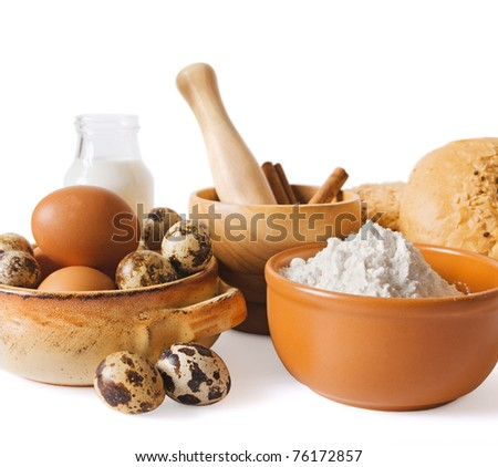 Composition with a milk bottle, eggs and a flour on a white background