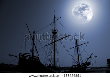 Composition with a silhouette of an old discovery times caravel in a full moon night. - stock photo