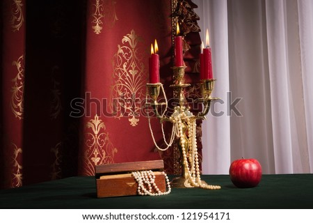 Composition with apple, candlestick and jewellery box on red background