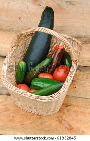 Composition with basket and vegetables on a wooden background - stock photo