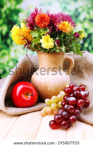 Composition with beautiful flowers in pitcher, and fruits,  on bright background