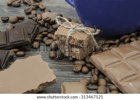 Composition with blue cup, coffee beans and chocolate - stock photo