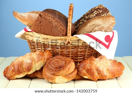 Composition with bread and rolls, in wicker basket on wooden table, on color background - stock photo