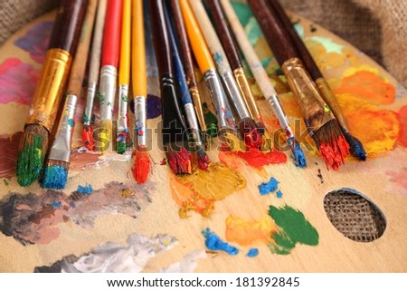 Composition with brushes on used wooden palette, on wooden background
