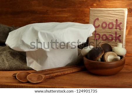 Composition with chef's hat on wooden background - stock photo