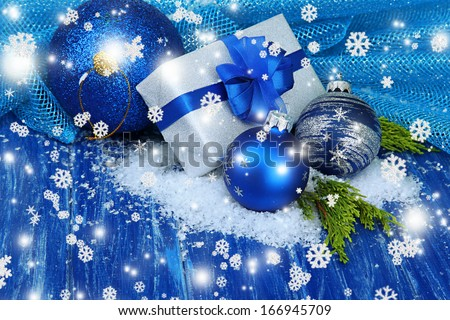 Composition with Christmas balls, gift box and snow on color wooden background