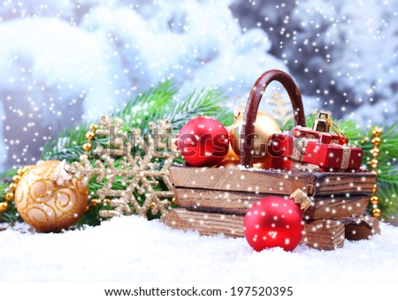 Composition with Christmas decorations in basket, fir tree on light background - stock photo