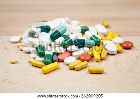 Composition with colorful pills and wooden background