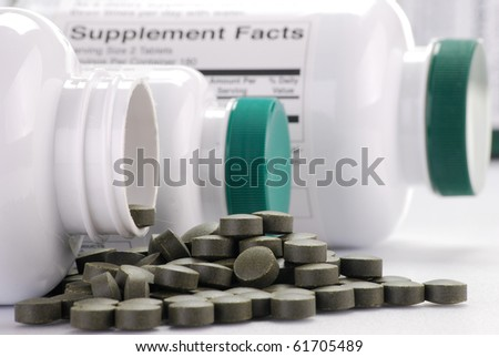Composition with containers of dietary supplements and chlorella pills - stock photo
