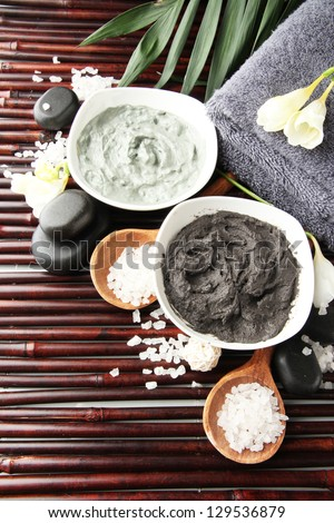 Composition with cosmetic clay for spa treatments, on bamboo background - stock photo