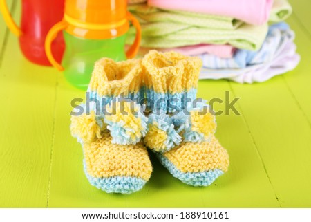 Composition with crocheted booties for baby,clothes, bottles on wooden background - stock photo