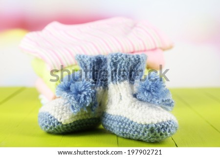 Composition with crocheted booties for baby, clothes on color table, on light  background - stock photo