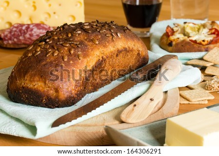 Composition with crusty bread, yellow cheese, butter, salami and red wine