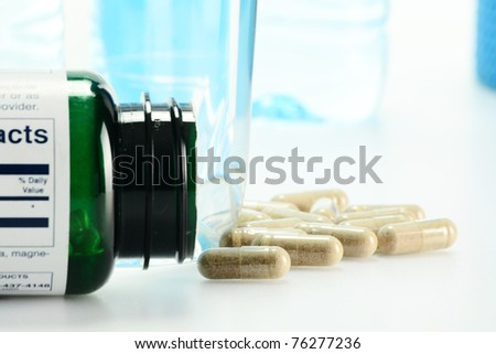 Composition with dietary supplement capsules and glass of water - stock photo