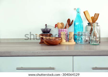 Composition with different utensils on wooden wooden table in kitchen - stock photo