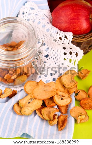 Composition with dried apples in glass jar  and fresh apples in basket, on napkin, on bright background - stock photo