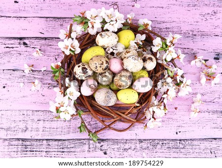 Composition with Easter eggs and blooming branches in nest, on wooden background - stock photo