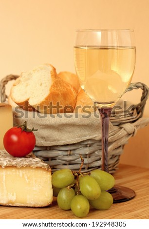 Composition with french wine, cheese and grape on wooden table