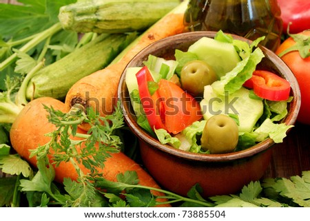 Composition with fresh raw vegetables and Healthy Fresh Salad on a wooden table. background with a salad and vegetables