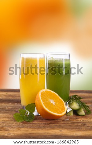 Composition with glass of orange and cucumber juice  - stock photo