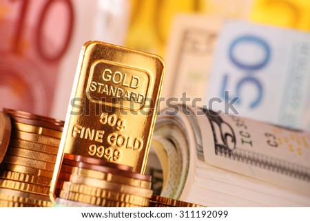 Composition with 50 gram gold bar, banknotes and coins.  - stock photo