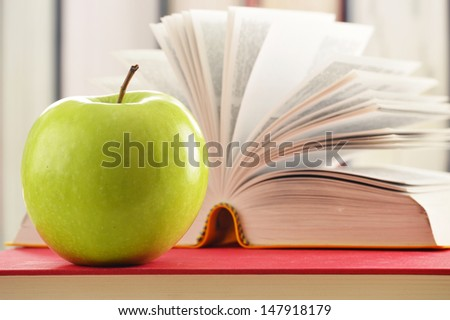 Composition with green apple and books on the table - stock photo