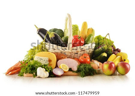 Composition with groceries in wicker basket on kitchen table - stock photo
