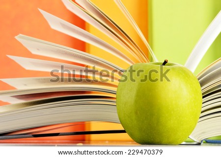 Composition with hardcover books and apple in the library - stock photo