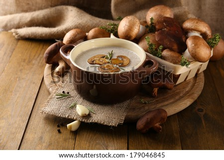 Composition with mushroom soup in pot, fresh and dried mushrooms, on wooden table, on sackcloth background - stock photo