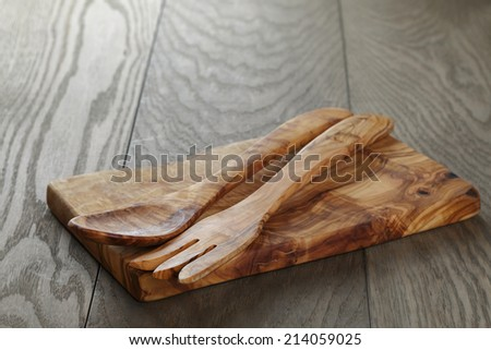 composition with olive kitchen utensils on top of oak table, rustic background - stock photo