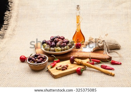 Composition with olive wood, olives, vinegar and spices with burlap texture in the background - stock photo