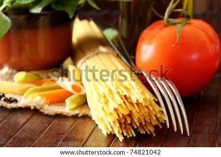 Composition with raw pasta,vegetables ,olive oil and herbs - stock photo