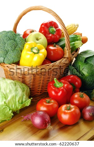 Composition with raw vegetables and wicker basket on kitchen table - stock photo