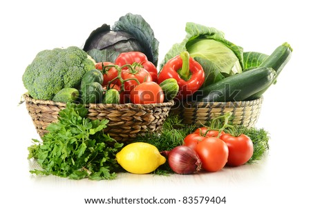 Composition with raw vegetables and wicker baskets isolated on white