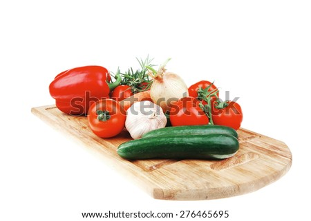 Composition with raw vegetables on kitchen cut board isolated over white background - stock photo