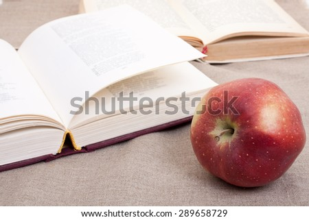 Composition with red apple and opened books on the table, on the decorative linen cloth. - stock photo