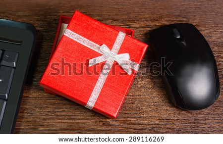 Composition with red gift box,  mouse and keyboard laying on wooden desk - stock photo