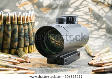 Composition with rifle ammunition and red dot sight. - stock photo