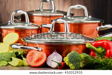 Composition with set of pots and raw vegetables.