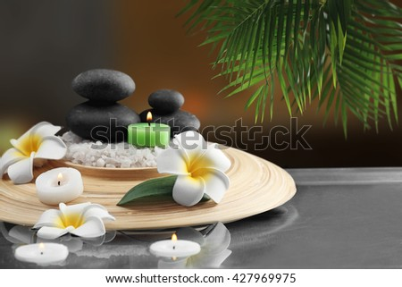 Composition with spa stones and plumeria on blurred background - stock photo