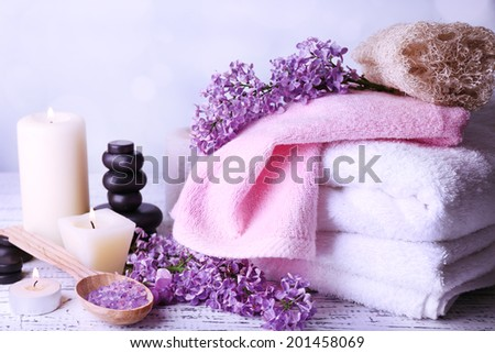 Composition with spa treatment, towels and lilac flowers, on light background - stock photo