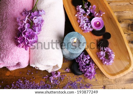 Composition with spa treatment, wooden bowl with water, towel and lilac flowers, on wooden background - stock photo