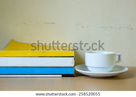 Composition with stack of books and coffee cup on table - stock photo
