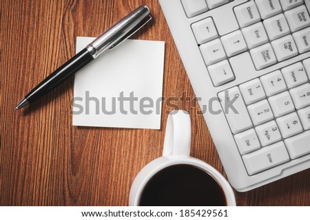 Composition with sticker, the cup of coffee, pen and keyboard laying on wooden desk - stock photo