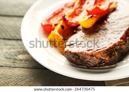 Composition with tasty roasted meat  and vegetables on plate, on wooden background - stock photo