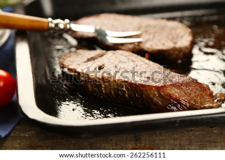 Composition with tasty roasted meat on pan, tomatoes and rosemary sprigs on wooden background - stock photo